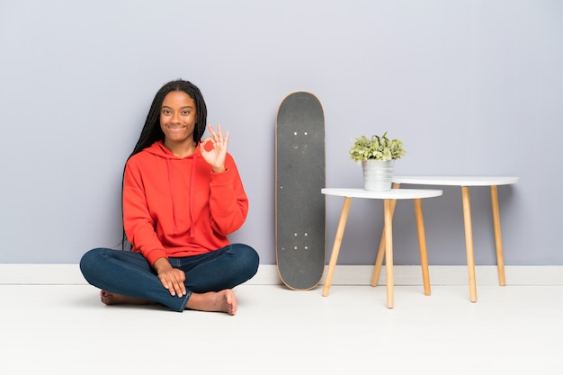 African american skater teenager girl with braided hair sitting on the floor showing an ok sign with fingers