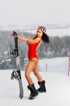즐거운 얼굴 표정으로 스노우 보드 안경 수영복에 아프리카 계 미국인 스키어 여자