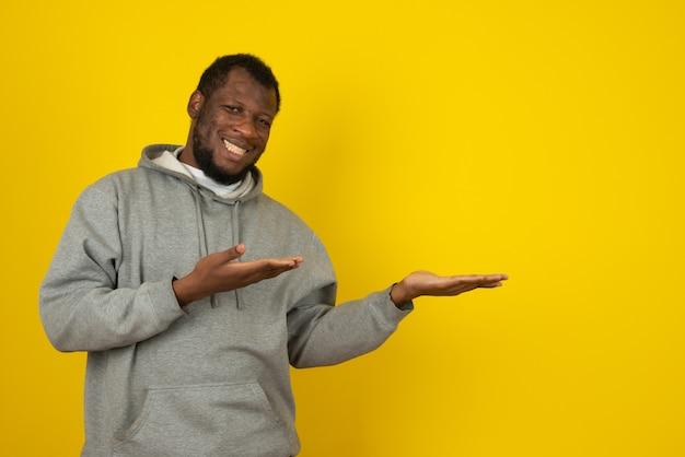 Uomo sorridente afroamericano che ha aperto le mani, in piedi davanti al muro giallo.