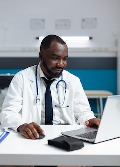 コンピューターの画面を見ているアフリカ系アメリカ人の専門セラピスト医師