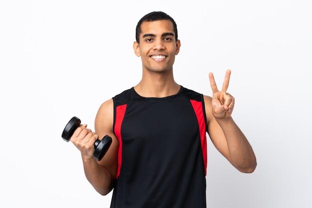 Афро-американский спортивный человек над белой стеной, улыбаясь и показывая знак победы