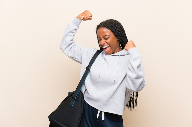 African american sport teenager girl with long braided hair celebrating a victory