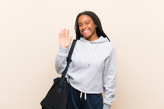 African american sport teenager girl with long braided hair saluting with hand with happy expression