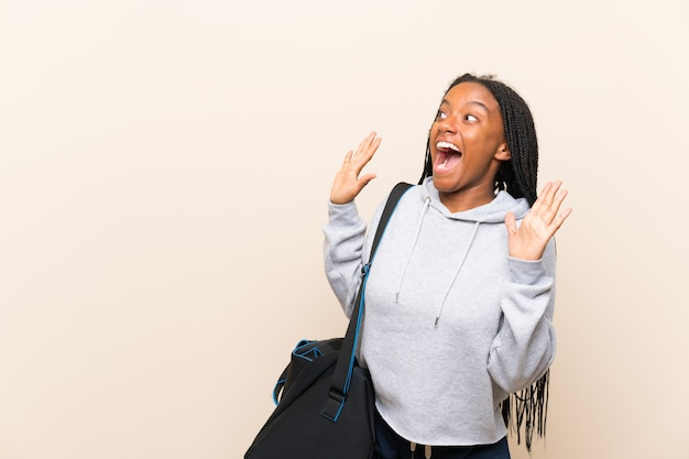 African american sport teenager girl with long braided hair with surprise facial expression