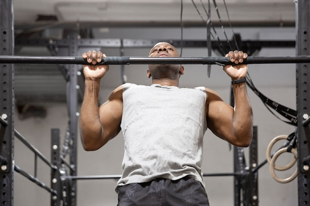 African american sportsman doing physical exercise on fixed bar. fitness training in gym.