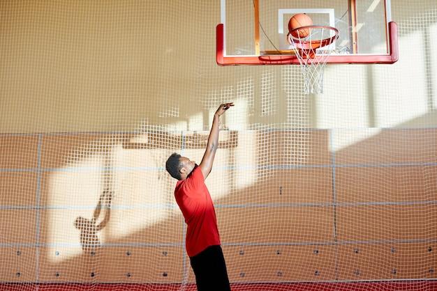 African-american sportsman shooting goal