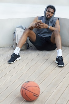 屋外でスマートフォンを使用するアフリカ系アメリカ人のスポーツマン