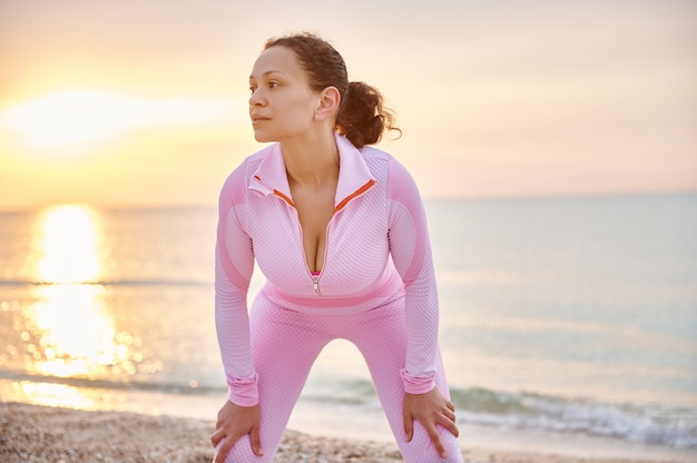 African american sportswoman resting after jogging on the sea background