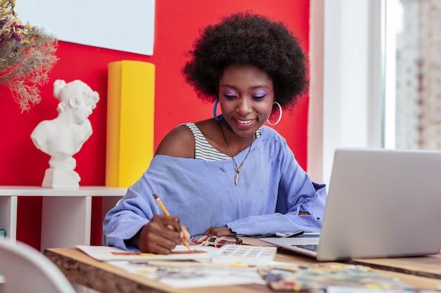 아프리카 계 미국인 학생. 그녀의 노트북을 사용하여 공부하는 동안 즐거운 느낌이 아프리카 계 미국인 학생