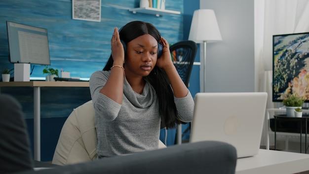 Афро-американский студент-блогер надевает наушники, работая удаленно из дома
