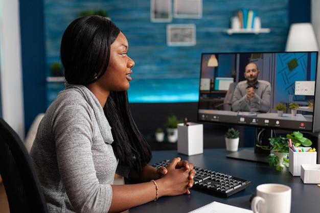 遠隔地の学校の同僚とマーケティングクラスのアイデアについて話し合うアフリカ系アメリカ人の学生