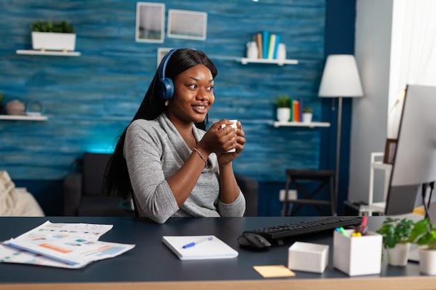 現代の音楽を聴きながらヘッドフォンを身に着けている手でコーヒーのカップを保持しているアフリカ系アメリカ人の学生...