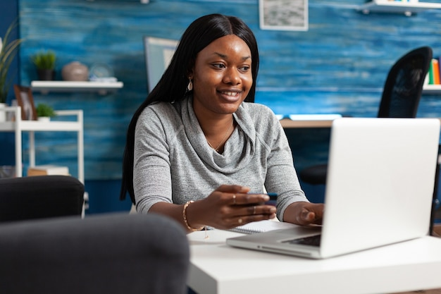 African american student making online sale shopping holding economy credit card in hands