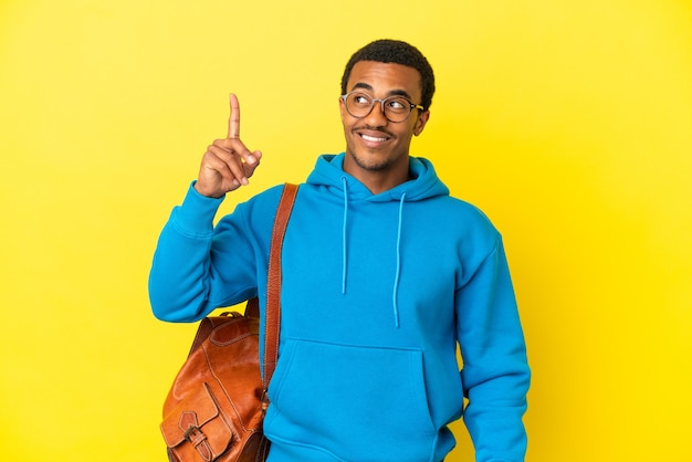 African american student man over isolated yellow background intending to realizes the solution while lifting a finger up
