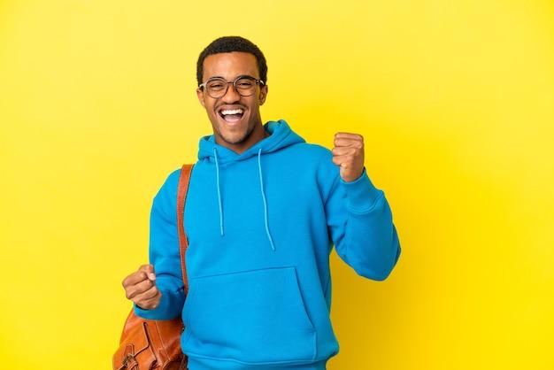 승리를 축하하는 고립된 노란색 배경 위에 아프리카계 미국인 학생 남자