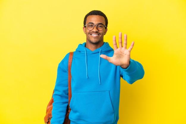 손가락으로 다섯을 세는 고립된 노란색 배경 위에 아프리카계 미국인 학생 남자
