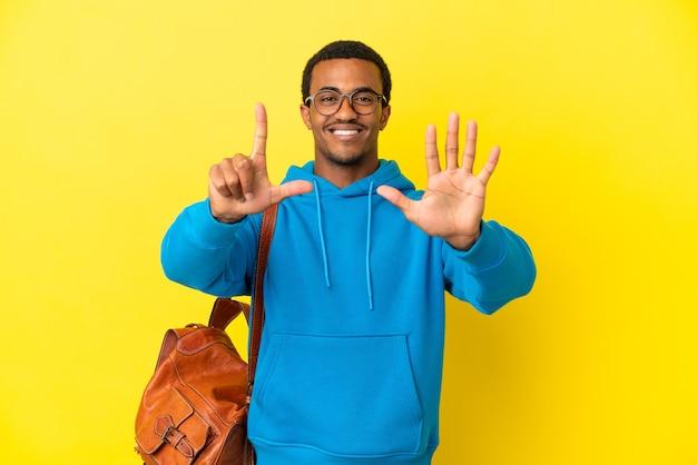 Афро-американский студент человек на изолированном желтом фоне считает семь пальцами