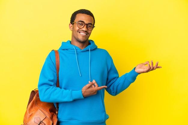 격리된 노란색 배경 위에 있는 아프리카계 미국인 학생 남자가 초대하기 위해 손을 옆으로 내밀었습니다.