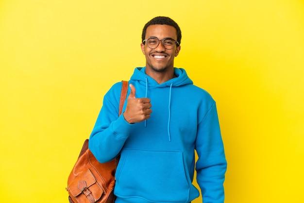 고립 된 노란색 배경 위에 엄지손가락 제스처를 주는 아프리카계 미국인 학생 남자
