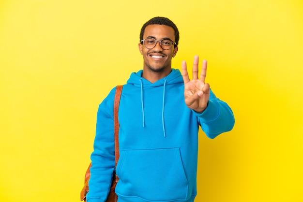 고립 된 노란색 배경 위에 아프리카 계 미국인 학생 남자 행복 하 고 손가락으로 세 세