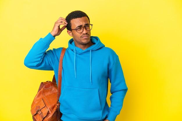 疑いを持って、混乱した表情で孤立した黄色の背景上のアフリカ系アメリカ人の学生男