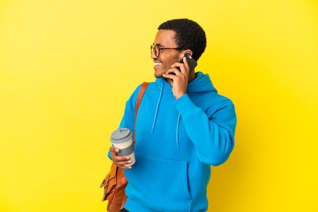 Афро-американский студент мужчина на изолированном желтом фоне держит кофе на вынос и мобильный