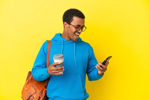 고립된 노란색 배경 위에 있는 아프리카계 미국인 학생 남자가 테이크아웃 커피와 모바일을 들고