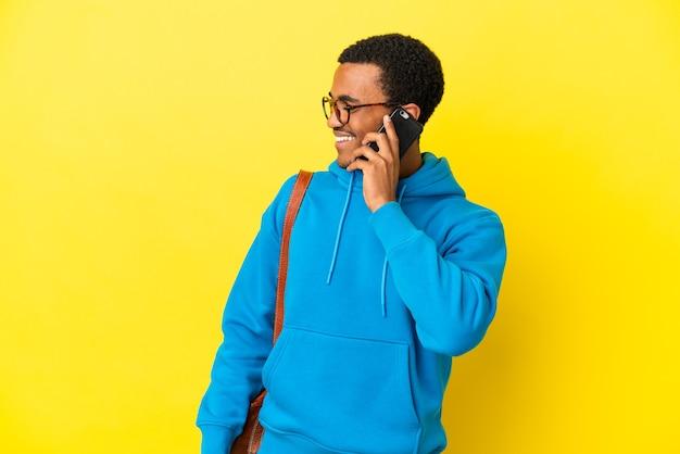 고립된 노란색 배경 위에 있는 아프리카계 미국인 학생 남자는 누군가와 휴대폰으로 대화를 유지하고 있습니다.