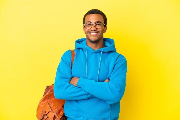 Афро-американский студент мужчина на изолированном желтом фоне, скрестив руки в лобном положении
