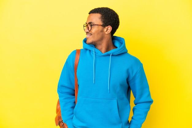 Афро-американский студент человек на изолированном желтом фоне, глядя в сторону