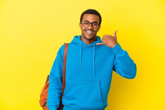 Афро-американский студент человек на изолированном желтом фоне, делая телефонный жест. перезвони мне знак