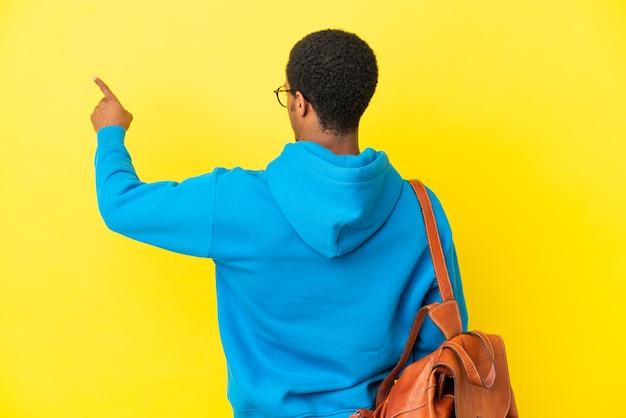 Афро-американский студент человек на изолированном желтом фоне, указывая указательным пальцем назад