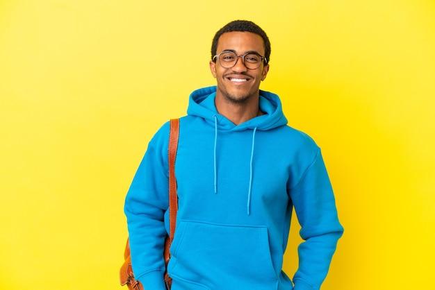 Афро-американский студент человек на изолированном желтом фоне позирует с руками на бедрах и улыбается