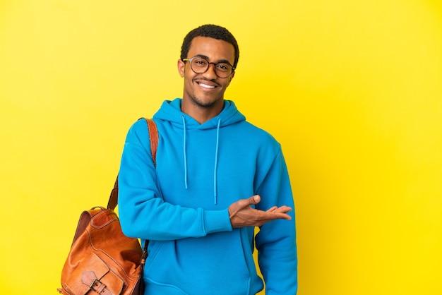 외진 노란색 배경 위에 있는 아프리카계 미국인 학생 남자가 웃고 있는 동안 아이디어를 제시합니다.