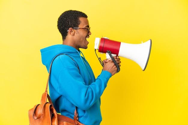 확성기를 통해 외치는 고립된 노란색 배경 위에 아프리카계 미국인 학생 남자