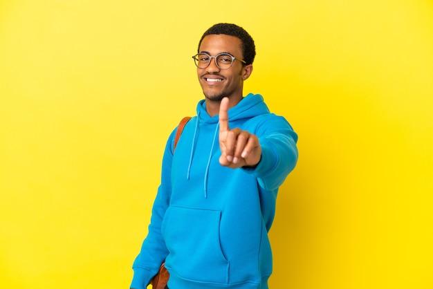 Афро-американский студент человек на изолированном желтом фоне показывает и поднимает палец