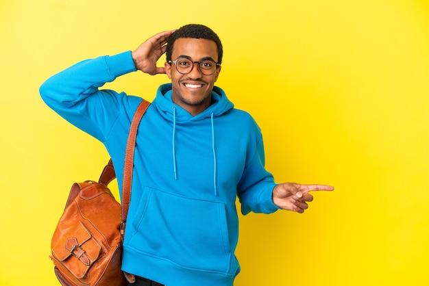 고립된 노란색 배경 위에 있는 아프리카계 미국인 학생 남자가 놀라 옆으로 손가락을 가리켰다