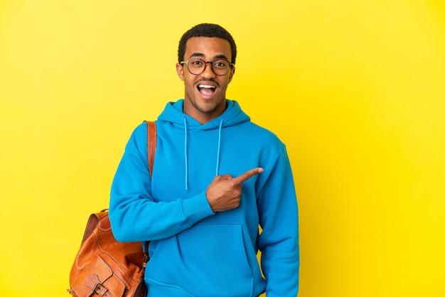 고립 된 노란색 배경 위에 아프리카 계 미국인 학생 남자 놀라고 가리키는 측면