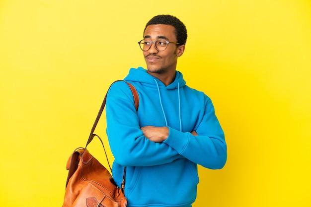 Афро-американский студент человек на изолированном желтом фоне со скрещенными руками и счастливым