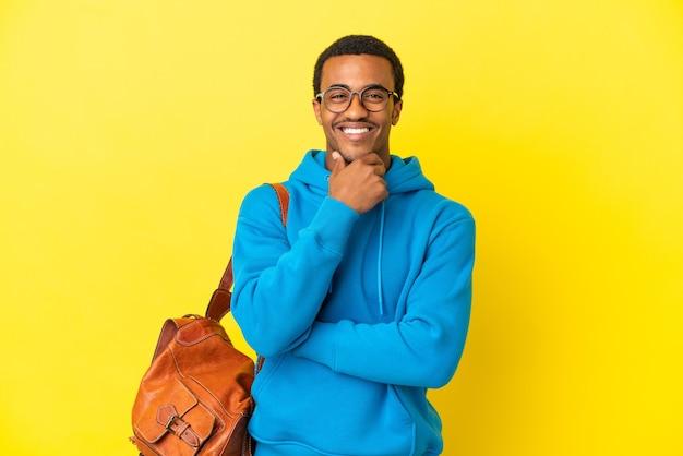 Афро-американский студент человек на изолированном желтом фоне в очках и счастливым