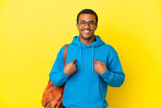 놀란 표정으로 고립된 노란색 배경 위에 아프리카계 미국인 학생 남자