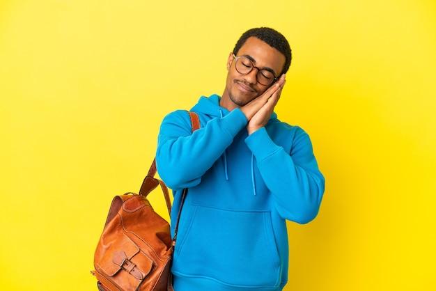 愛らしい表情で睡眠ジェスチャーを作る孤立した黄色の壁の上のアフリカ系アメリカ人の学生男