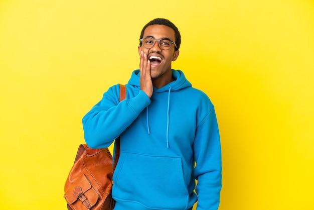 Афро-американский студент-мужчина над изолированной желтой стеной с удивленным и шокированным выражением лица