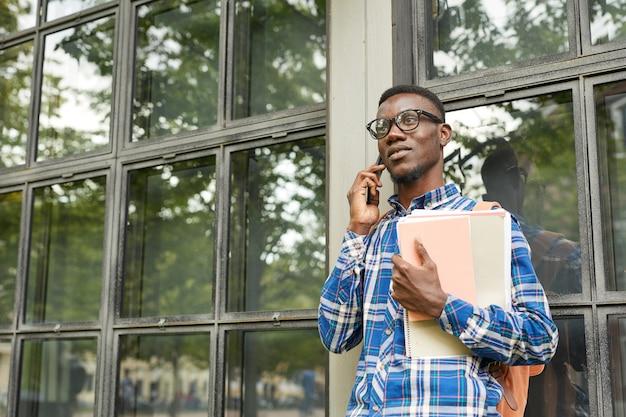 Афро-американский студент говорит по телефону