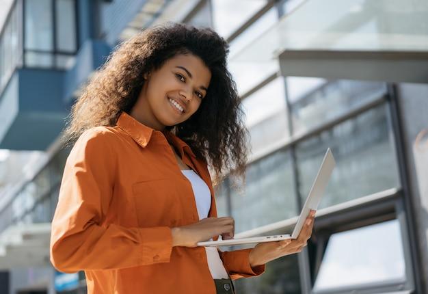 アフリカ系アメリカ人の学生が現代のテクノロジーとインターネットを使用して勉強しています。オンライン教育のコンセプト