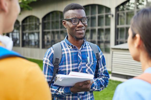 Афро-американский студент разговаривает с друзьями на свежем воздухе