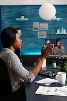 オンラインビデオ通話会議中に遠隔地の学校の同僚を振っているアフリカ系アメリカ人の学生