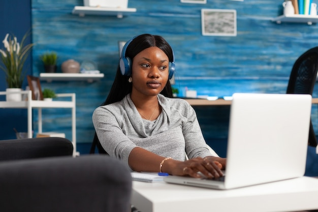 Афро-американский студент в наушниках во время образовательного веб-семинара удаленно работает при общении ...