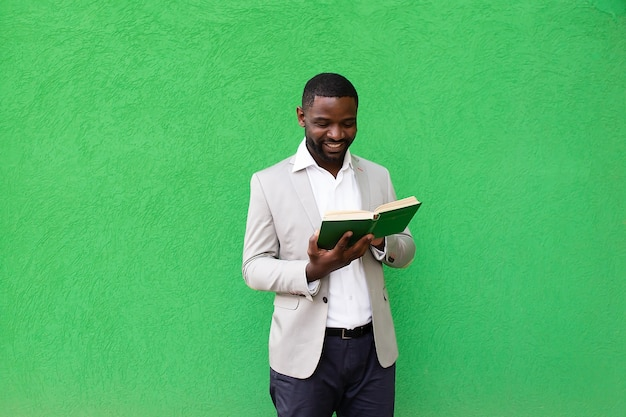 The african american student with a book on a green background