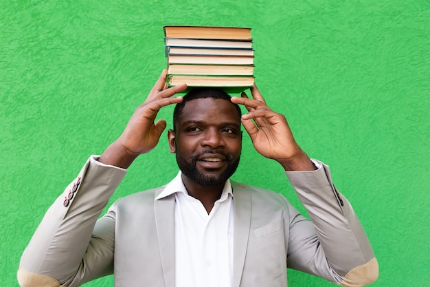 African american student with a book on a green background